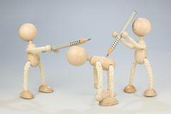 Bullying. Two wooden dolls attacks another one with pencils Royalty Free Stock Photography