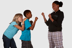Bullying Kids. Three kids over white one girl hiding behind boy who is protecting her from a bigger kid to show bullying in school royalty free stock photos