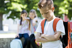 Bullying after school. Two little girls poting at the little sad boy, focus on foreground Royalty Free Stock Photo