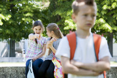 Bullying after school. Two little girls poting at the little sad boy, focus on background Stock Photos