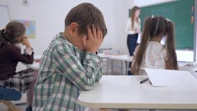 Bullying, tired schoolboy sits at a desk in classroom on background of classmates and female teacher near blackboard
