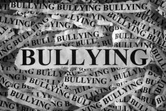Bullying. Torn pieces of paper with the word Bullying. Concept Image. Black and White. Closeup royalty free stock images