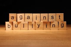 Against bullying words written on wood cube Royalty Free Stock Photo