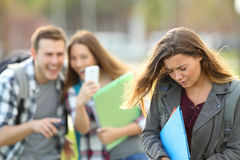 Bullying victim being recorded by classmates. Bullying victim being video recorded on a smartphone by classmates in the street with a unfocused background royalty free stock photography