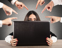 Bullying on the web. People pointing a girl hidden behind a computer Stock Photos