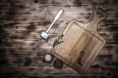 Bulta för att slå köttet, örterna och kryddorna på ljus träcu royaltyfri fotografi