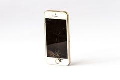 Bulta och en smartphone med en bruten skärm royaltyfria bilder