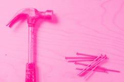Bulta och spikar i bakgrunden av kryssfaner Plan sikt Tonade rosa färger Begrepp av feminism arkivbilder