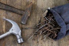 Bulta och spikar på en träseminariumtabell Snickeritillbehör royaltyfri fotografi
