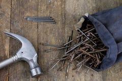Bulta och spikar på en träseminariumtabell Snickeritillbehör arkivfoton