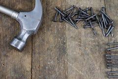 Bulta och spikar på en träseminariumtabell Snickeritillbehör royaltyfri foto
