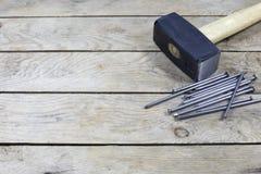 Bulta och spikar på träbräde arkivfoton