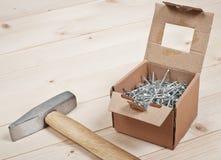 Bulta och spikar på träplankor arkivbilder