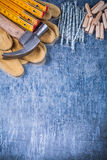 Bulta skyddande handskar som trämeterbunten av metall spikar och D royaltyfri foto