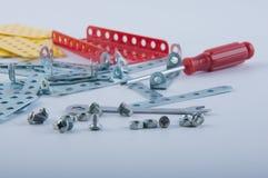 Bultar, skruvmuttrar, skruvmejseln och metalliska delar lägger på vit bakgrund Fotografering för Bildbyråer