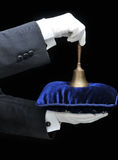 Bulter with Service Bell on Pillow. Butler holding a velvet pillow and a service bell - hands and arms only Stock Photo