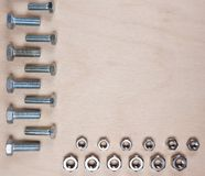 Bultmuttrar skruvar isolerat på träbakgrund arkivbild