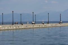 Bulwar morze przeciw górom z ławkami, Zdjęcie Royalty Free