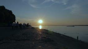 Bulwar z grupami ludzi sylwetka piękny zachód słońca na plaży zbiory wideo
