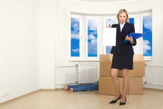 Bum-bailiff. A business woman produces a warrant a debtor in a room Stock Image
