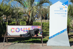 BUM. SOCHI, RUSSIA - MAR 23, 2014: The HOMELESS man sleeping on a bench in the city street Royalty Free Stock Photos