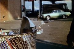 Bum taking shoe out of trash can stock footage