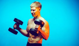 Bumbbell training male. Sexy body man indoor Royalty Free Stock Image