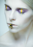 Bumblebee: model with creative make-up and bug on her lips Stock Images