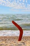 Bumerang na piaskowatej plaży przeciw morza niebieskiemu niebu i fala Obraz Stock