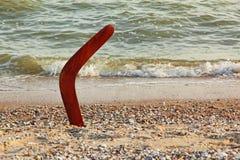 Bumerang på den sandiga stranden nära havsbränning Royaltyfri Bild