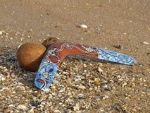 Bumerang y coco en una arena. Foto de archivo
