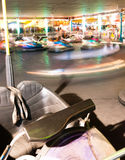 Bumper Cars Amusement Park Ride Blurred Motion. One sits unused while other bumper cars whirl around the track royalty free stock photos
