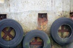 Bumper, oude banden in de vissershaven Stock Fotografie