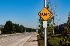 Bumps road sign next to an industrial byway. And a blue sky royalty free stock photos