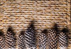 Bumps on a wicker background. Pine cones on a wicker basket royalty free stock image