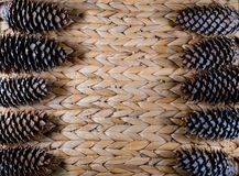 Bumps on a wicker background. Pine cones on a wicker basket royalty free stock photo