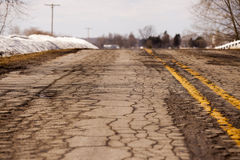 Bumpy Michigan Roads in Winter. An image of a pot holed road, criss crossed with cracks in a brutal Michigan winter Royalty Free Stock Photos
