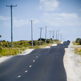 Bumpy Road. Very bumpy rough road with power lines and blue sky Royalty Free Stock Images
