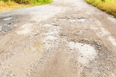 Bumpy road. Close up bumpy stone road with water in potholes royalty free stock photography