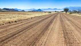 Bumpy road to success and through the african desert. Adventurous drive on a rough gravel road through the desert towards the mountains Stock Image