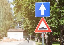 Bumpy road traffic sign. Sunny weather, cyclist on the road stock image