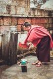 Bumthang,不丹- 2016年9月14日:在Kurjey Lhakhang (版本记录寺庙附近的修士洗涤的盘)在Bumthang谷,不丹 图库摄影