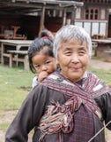 Bumthang Bhutan - September 14, 2016: Gammal bhutanesisk kvinna som tillbaka bär ett barn på henne i en by i den Bumthang dalen,  Arkivfoton
