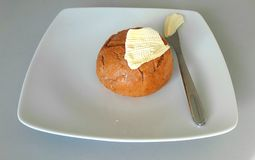 Bun baked with margarine on a plate. Bun baked, whole, round with margarine and knife on a plate Stock Photo