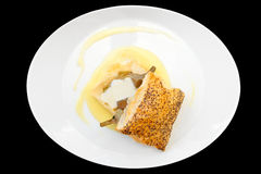 Bun with braised artichoke on oval plate isolated on black Stock Image