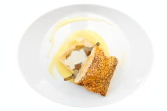 Bun with braised artichoke on oval plate isolated on white Royalty Free Stock Images