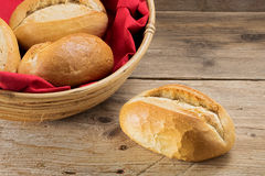 Bun and bread rolls in a basket with red napkin on old wood Stock Images