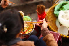 Bun cha or pho soup, street food in Vietnam. Woman eating Bun cha or pho soup, street food in Vietnam royalty free stock images