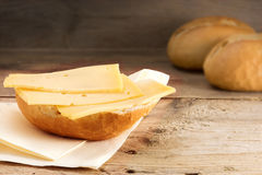 Bun with cheese and blurry bread rolls in the background on wood Royalty Free Stock Image