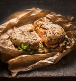 Bun with chicken, cheese and lettuce in a crumpled paper on rustic wooden background. Bun with chicken, cheese and lettuce in crumpled paper on rustic wooden stock photography